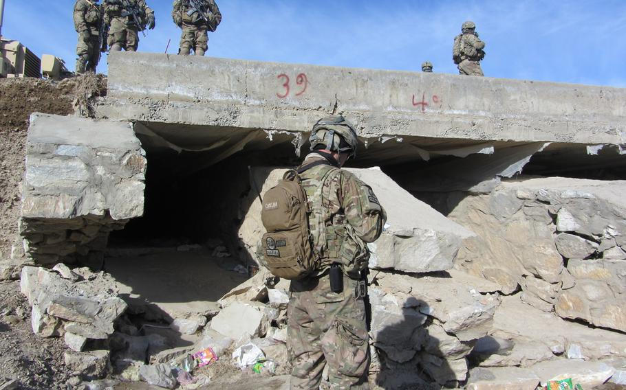 Servicemembers inspect an open culvert in Afghanistan. A report released by the Special Inspector General for Afghanistan Reconstruction on July 23, 2013, detailed fraud and negligence in the installation of grates to block insurgents from placing bombs in culverts running under roads.