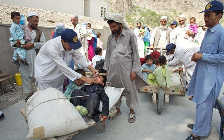Workers vaccinate young children during National Immunization Days in Afghanistan.