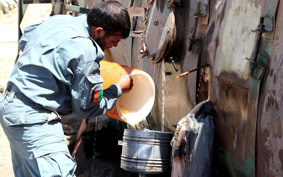 An Afghan National Policeman pours gasoline leaking from a fuel truck into barrels for the local people in Logar province, Afghanistan in this June 2010 photo.
