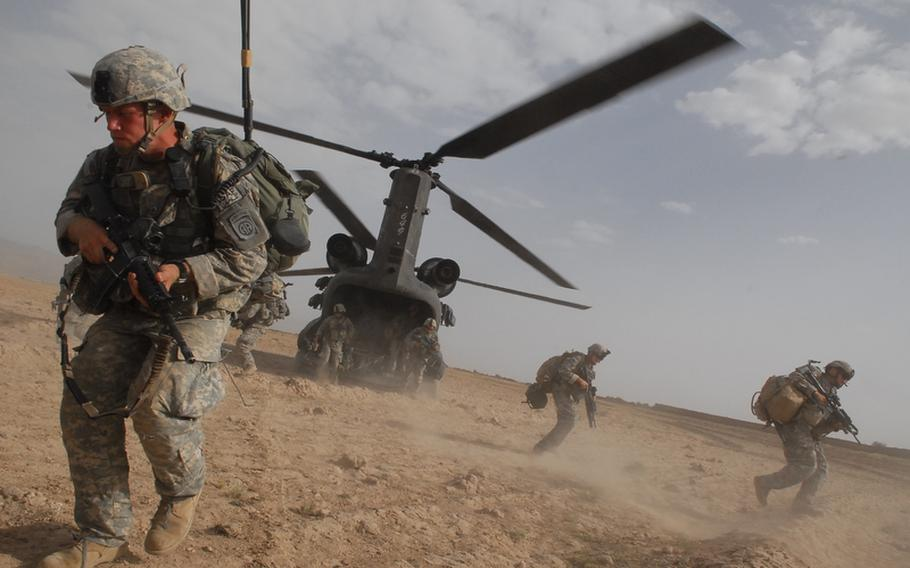 Spc. Colin Hankinson, 20, of Richardson, Texas, left foreground, hustles from the belly of a Chinook helicopter during a recent air assault in Zabul Province, Afghanistan.
