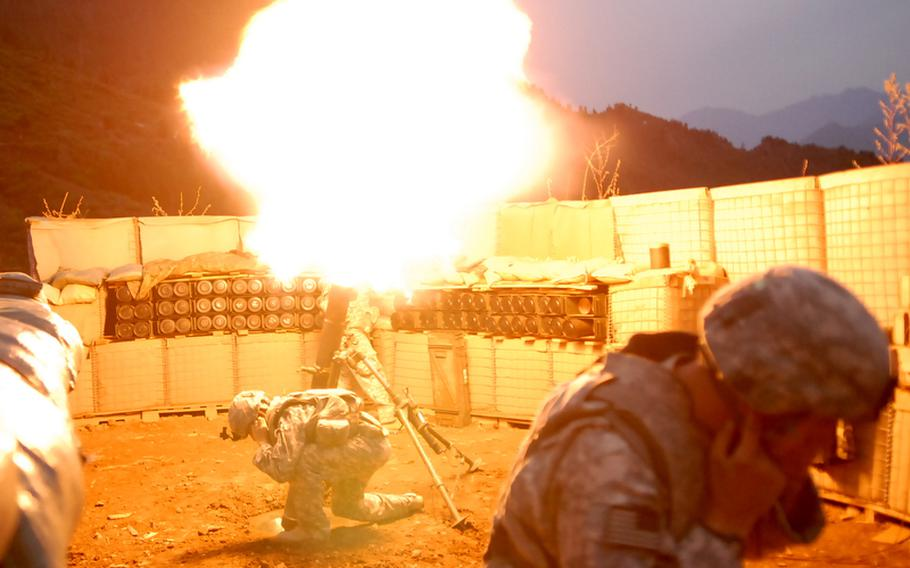 Soldiers at a combat outpost in Konar province's Gowardesh Valley fire a mortar in later September. With troops spread thin, units use air power and indirect fire to outgun insurgents.