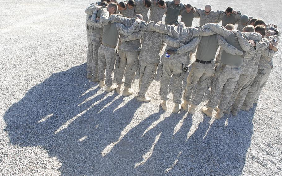 Soldiers with 4th Engineer Battalion, 62nd Engineer Sapper Company, 3rd Platoon pray before a mission conducted the day after their convoy was hit by three roadside bombs.