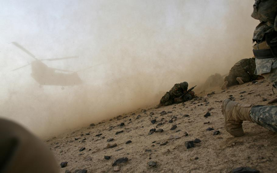 U.S. soldiers with Company C, 2nd Battalion, 508th Parachute Infantry Regiment and Afghan troops hug the ground as a CH-47 Chinook helicopter kicks up dust and rocks. It was lifting off outside the village of Shuyene Wusa, as part of a recent clearing operation in the Arghandab River valley, Kandahar province, Afghanistan.