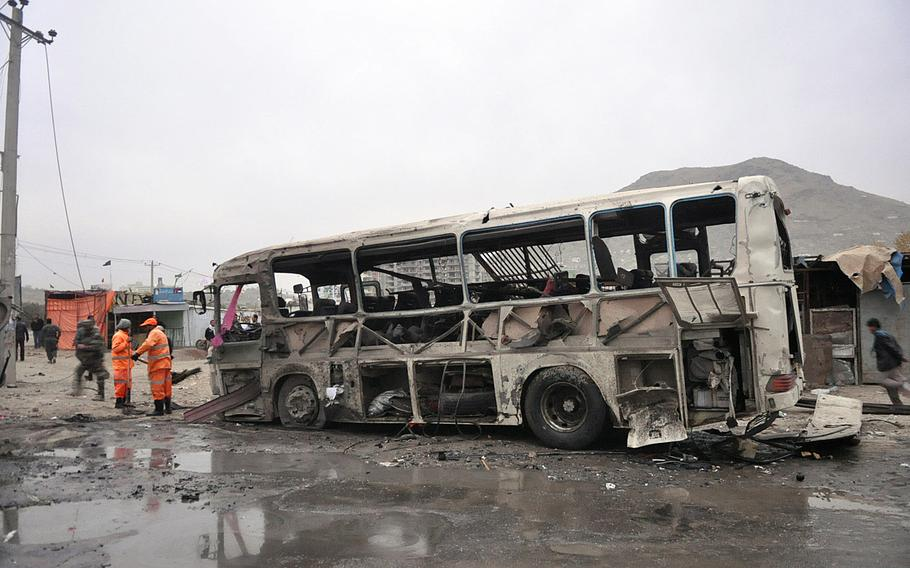 A civilian bus sits blown to pieces after a suicide car bomb attack in Kabul on Saturday, Nov. 16, 2013.  The attack took place just across the street from a popular literature university.