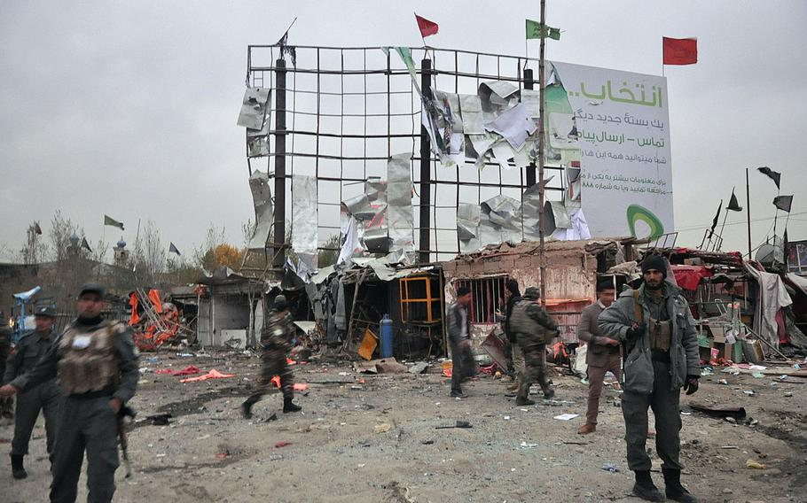 Afghan security forces stand guard near shops damaged in a suicide car bomb attack Saturday, Nov. 16, 2013, in Kabul near the site of a government-sponsored conference of elders convening Thursday to discuss a security pact that will determine whether U.S. troops stay in Afghanistan past 2014.