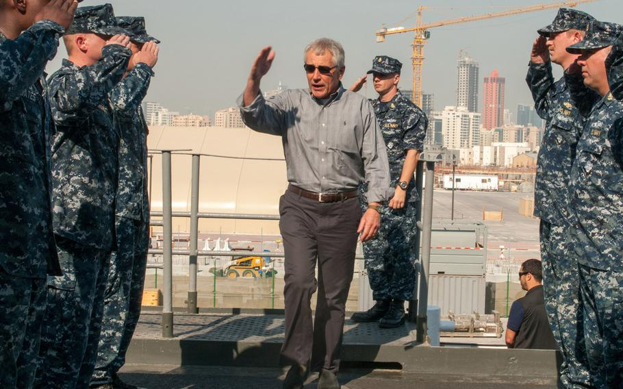 Defense Secretary Chuck Hagel salutes sideboys upon arriving aboard the afloat forward staging base USS Ponce Dec. 6, 2013. Hagel is currently visiting Bahrain to attend an annual meeting of Gulf-area defense chiefs.