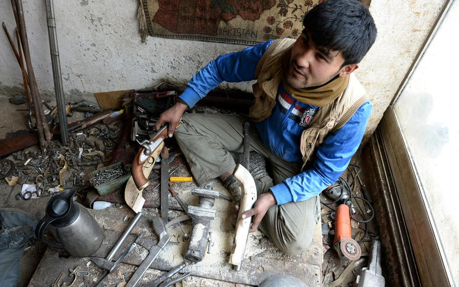 Nisar Ahmad, 22, shows examples of a finished replica pistol and one he is still working on in his workshop in Kabul. The tradition of making firearms by hand in Afghanistan dates to before the fight against British armies in the 19th century.