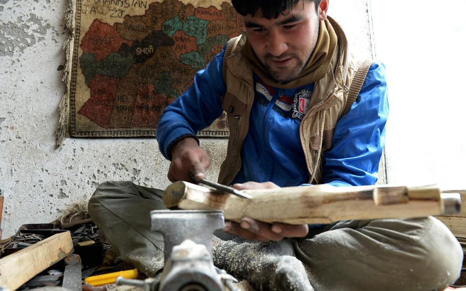 Nisar Ahmad, 22, carves the stock of a replica pistol in his workshop in Kabul. He says it can take up to a week to shape the stocks of larger guns like muskets and rifles.