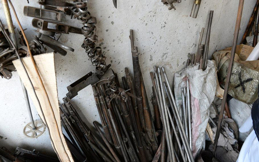 Old pieces of guns, pipes, and other scrap metal line the wall in a workshop in Kabul where craftsmen use the material to cobble together handcrafted replicas of early Afghan weapons like the jezail.
