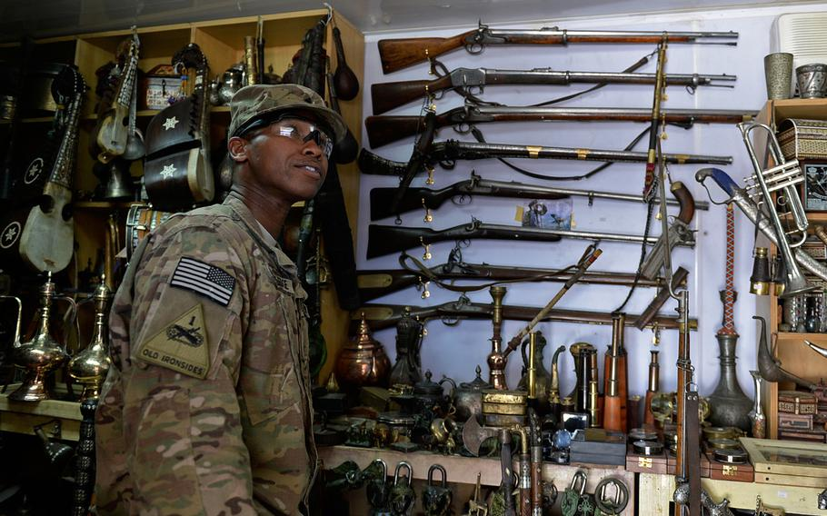 U.S. Army Sgt. Iraq Blackledge looks at knives and guns at an antique shop at Bagram Air Field in Afghanistan. He said he has been intrigued by the weapons but did not know until recently it was possible to mail such items back to the United States.