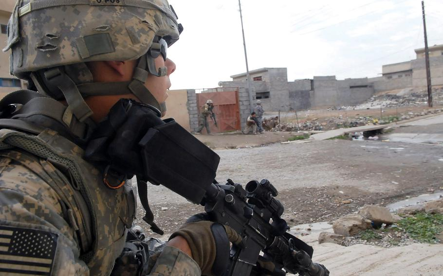 A U.S. soldier peeks out from behind a wall during a gunfight in Mosul, Iraq, in 2009.