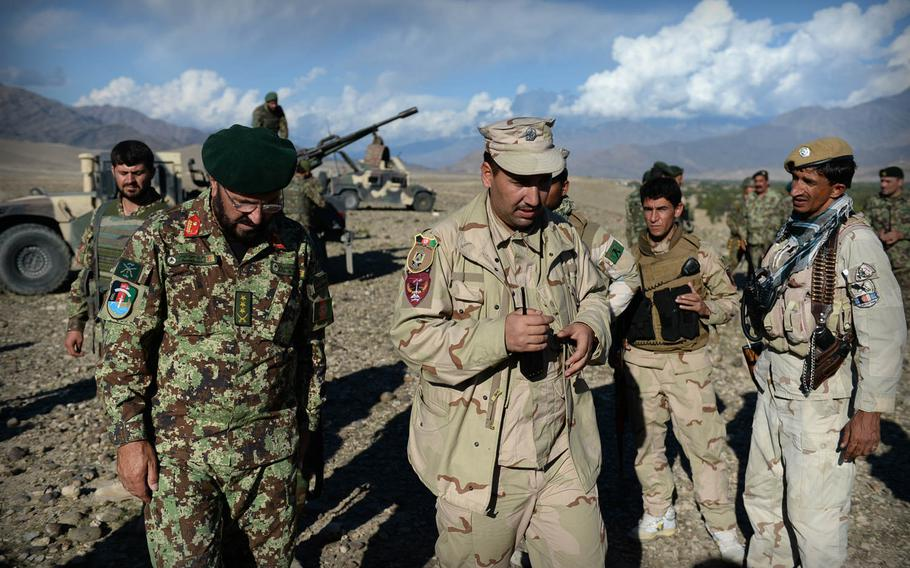 Afghan National Army Col. Hassani Kharokhel, left, and police Crisis Response Unit commander Rahm Khoda Mokhlis, center, discuss their plans during a joint clearing operation in Laghman province, Nov. 4, 2014. The restive province has seen ongoing low-level fighting between insurgents and government forces.