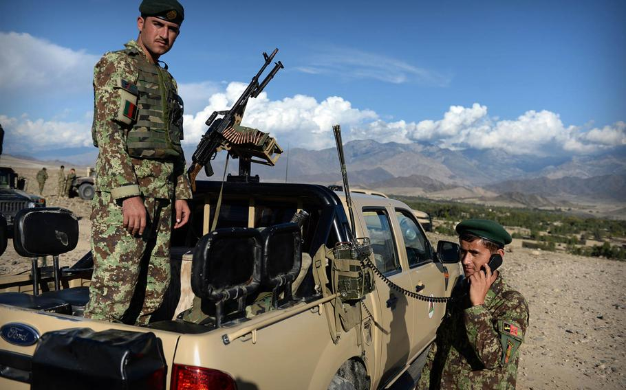 Afghan National Army soldiers help coordinate artillery fire during a joint clearing operation with police in Laghman province Nov. 4, 2014. Insurgents were still firing as troops packed up their equipment and ended the operation.