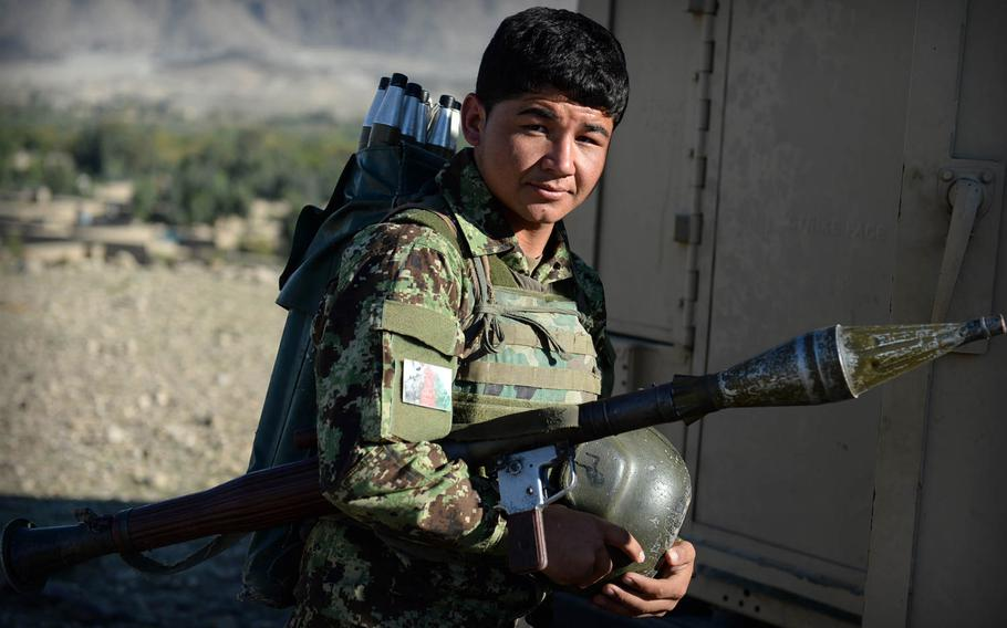 An Afghan National Army soldier prepares to board an armored Humvee after a clearing operation in Laghman province Nov. 4, 2014. The army provided back up for police units who engaged in firefights with insurgents in the valley below.