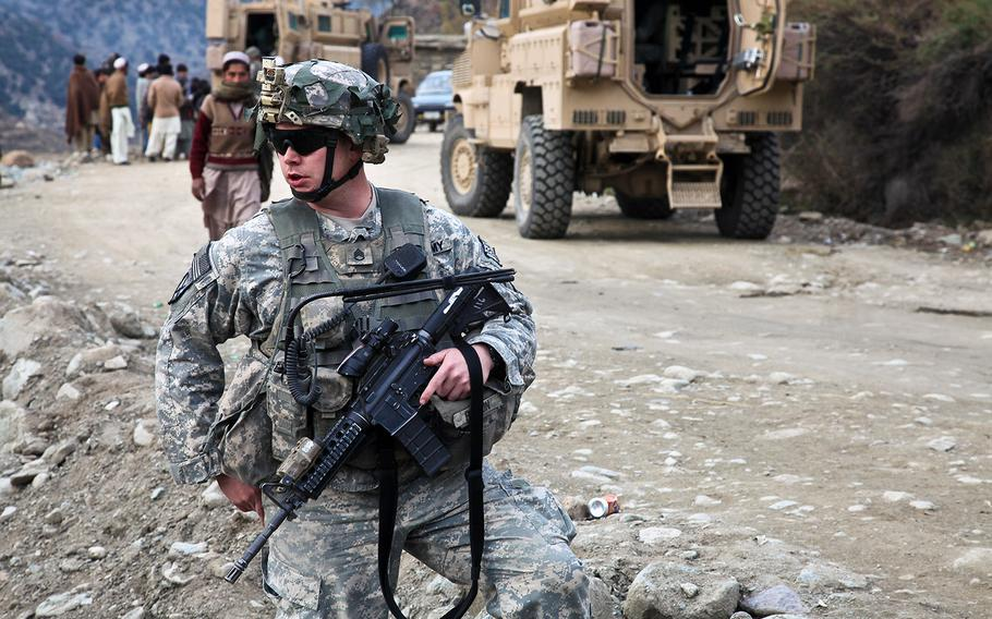 A U.S. soldier provides security for a convoy before leaving the district center in Dangam, Kunar province, Afghanistan, on Dec. 3, 2009. Afghan officials said Tuesday, Dec. 16, 2014, that Afghan army units deployed to eastern Kunar province to repulse a Taliban assault against security forces there.