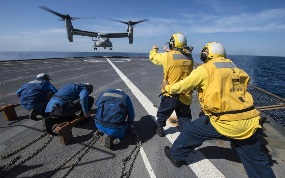 Sailors aboard the amphibious dock landing ship USS Fort McHenry signal an MV-22 Osprey to launch from the flight deck Jan. 11, 2015. Fort McHenry and the USS Iwo Jima have moved  into the Red Sea for a possible evacuation of U.S. Embassy workers from the Yemen capital of Sanaa.