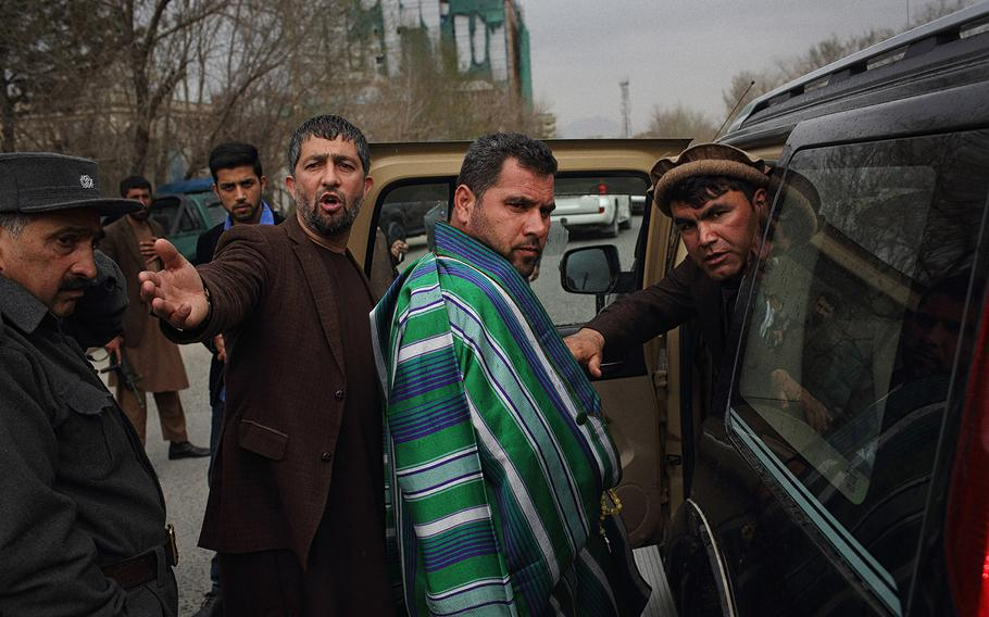 Najibullah Malikzadah, 37, center, is escorted by security officials after attending a condolence ceremony in a Kabul mosque on March 23, 2015. He is the elder brother of Farkhunda, who was beaten to death by a mob after being falsely accused of burning a Quran outside the Shah-do-Shamshira Mosque in central Kabul.