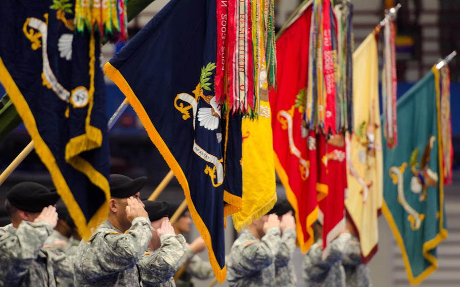 Battalion unit colors from the 1st Brigade Combat Team, 10th Mountain Division are displayed while saluting during a transformation ceremony held at Magrath Sports Complex on Fort Drum Oct. 17, 2014.