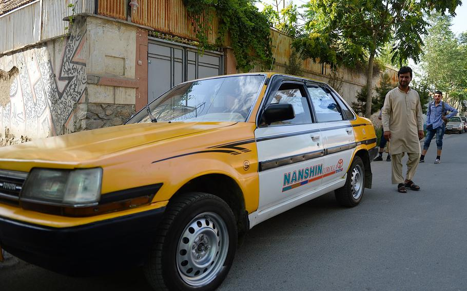 Kabul taxi driver Shir Shah heads for the driver's seat of his 1986 Toyota Corolla in the Tamani neighborhood of central Kabul. Since Toyota introduced the Corolla nearly 40 years ago, it has become the world's best-selling model with more than 40 million cars sold.