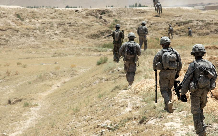 In this file photo taken July 6, 2011, U.S. Army and Afghanistan National Army soldiers patrol through the village of Baraki Barak, Logar province, Afghanistan, to clear a route and improve security in the area.