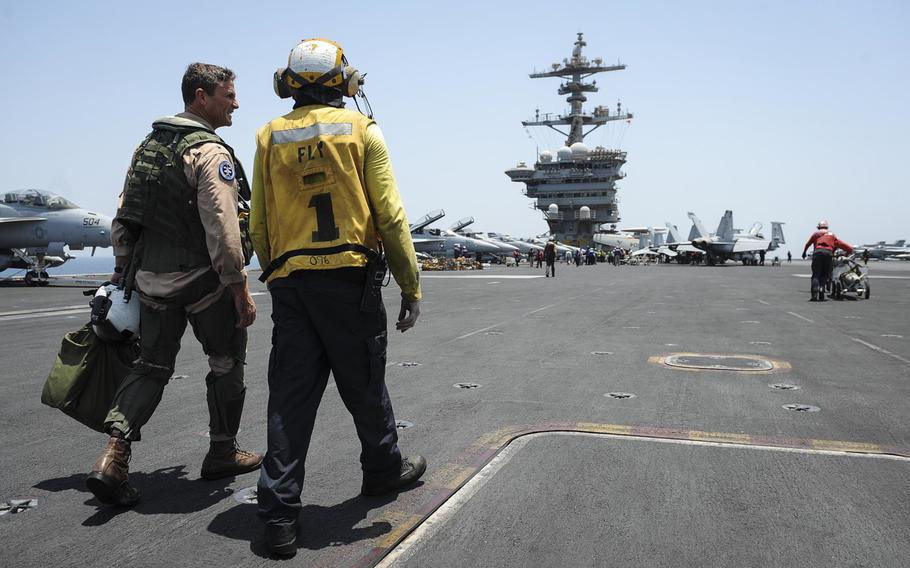 Rear Adm. Andrew Lewis, commander of Carrier Strike Group 12, talks to a sailor after his last flight aboard the aircraft carrier USS Theodore Roosevelt, which is deployed in the Persian Gulf, on July 17, 2015.