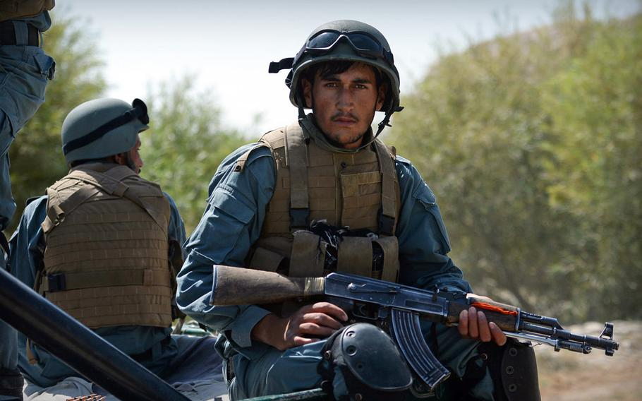 An Afghan policeman rides in the back of a truck during a patrol in Helmand province on Sept. 23, 2014. U.S. special forces have come back to Helmand in early to assist Afghan security forces, who have ceded ground to the Taliban since coalition forces left the province in late 2014.