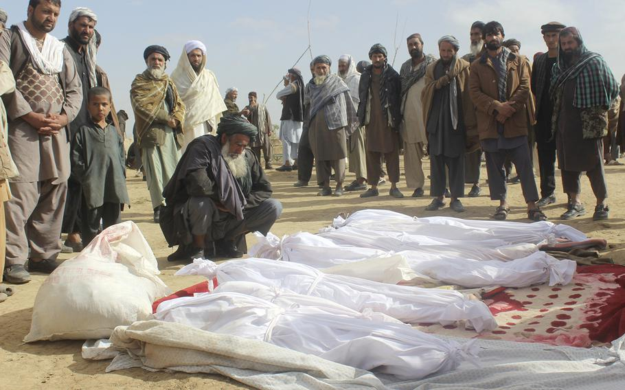 Afghan villagers gather around the bodies of civilians who were killed during clashes between Taliban and Afghan security forces in the Taliban-controlled, Buz-e Kandahari village in Kunduz province, Afghanistan, on Nov. 4, 2016.