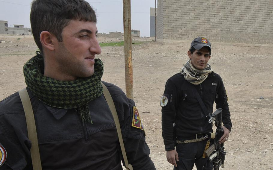 Yahia Majid Asa, right, a member of Iraq's Golden Division, wears a 5.11 Tactical sweater in eastern Mosul on Tuesday, Nov. 15, 2016, as his colleague Ahmed Faisal looks on. The brand has rapidly gained popularity among law enforcement and military personnel since its founding in 2003.