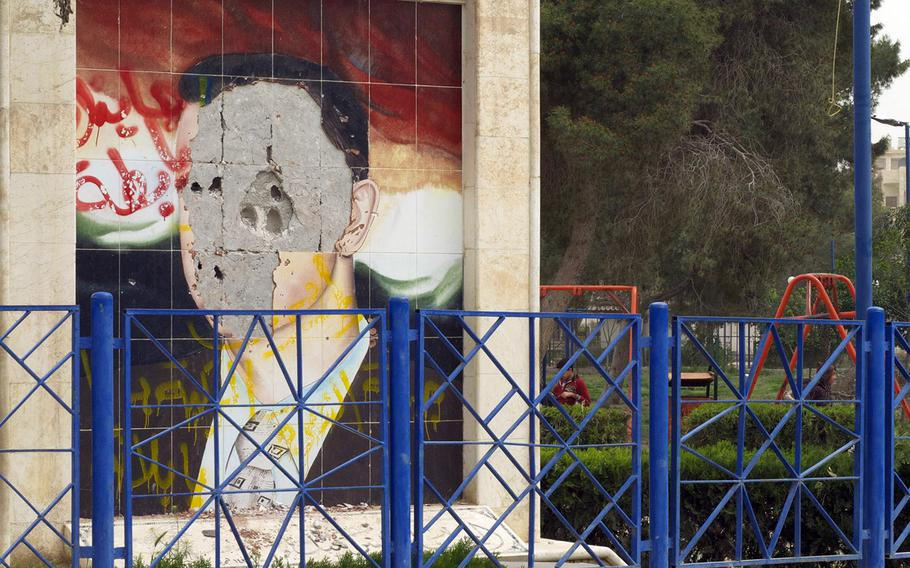 In a 2013 file photo, a defaced portrait of Syrian president Bashar Assad is seen on a wall in Raqqa, Syria.
