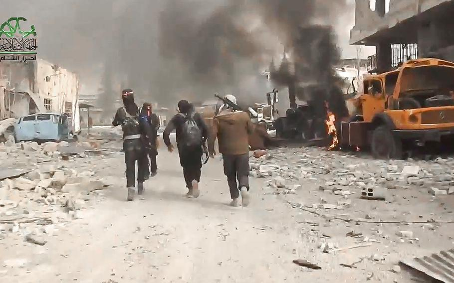 A screen grab from a video posted on Tuesday March 21, 2017, shows fighters from the Ahrar al-Sham militant group running past a buring truck during a battle against the Syrian government forces, in an eastern neighborhood of Damascus, Syria.