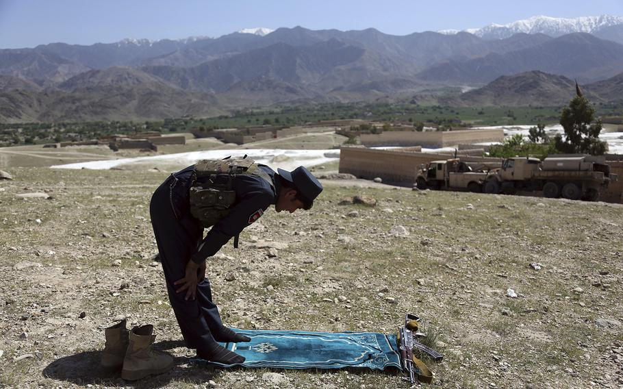 An Afghan security personnel prays in Pandola village near the site of a U.S. bombing in the Achin district of Jalalabad, east of Kabul, Afghanistan, Friday, April 14, 2017.