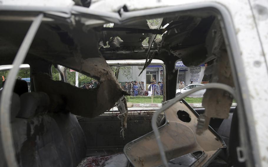 A crowd gathers around a damaged civilian vehicle at the site of a suicide attack in Kabul, Afghanistan, Wednesday, May 3, 2017.