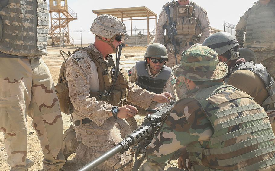 A Marine advisor with Task Force Southwest demonstrates proper firing techniques on a M2 Browning .50 Machine Gun to Afghan National Army soldiers with the Helmand Regional Military Training Center during a live-fire range at Camp Shorabak, Afghanistan, Aug. 17, 2017.