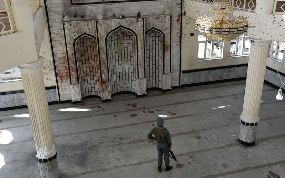An Afghan security official inspects the Imam Zaman mosque in Kabul, Afghanistan, on Saturday, Oct. 21, 2017, a day after an Islamic State suicide bomber attack.