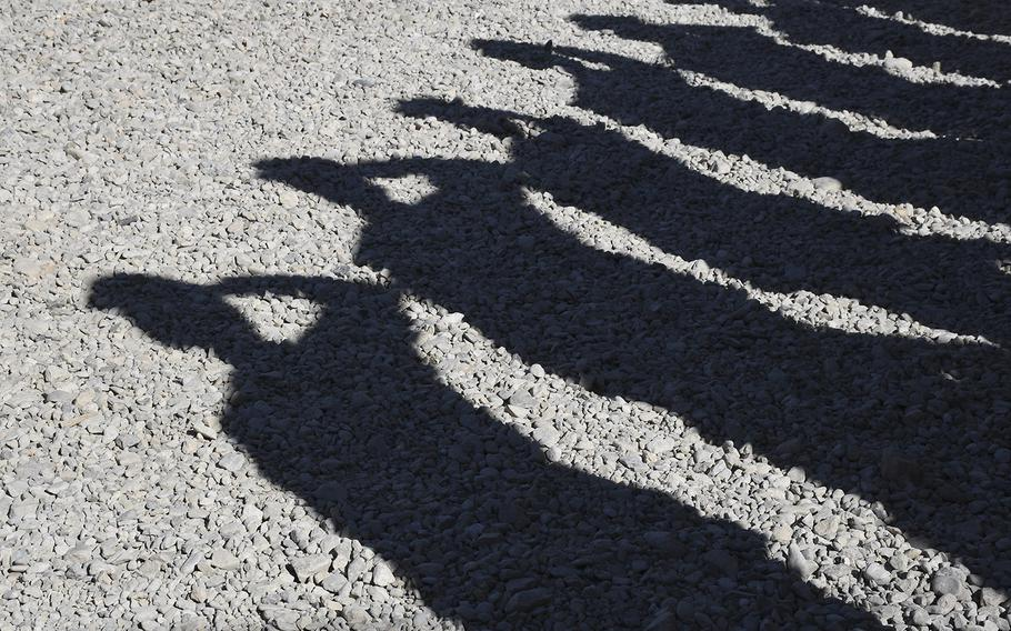 The shadows of a formation of Marines saluting during a transfer of authority ceremony for Task Force Southwest are seen at Camp Shorab in Helmand province, Afghanistan, on Monday, Jan. 15, 2018.