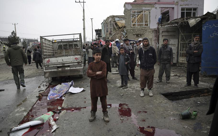 Residents walk through the site of a suicide attack in Kabul, Afghanistan, Friday, March 2, 2018. A large explosion in the eastern part of the Afghan capital on Friday morning killed at least one and wounded others officials said.