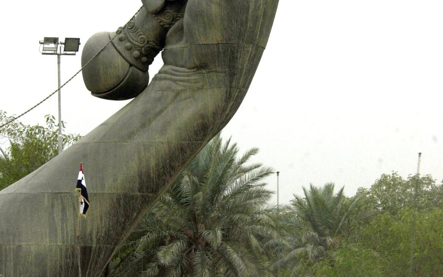 """Soldiers approach Saddam Hussein's famed Hands of Victory monument in Baghdad in April 2003. The monument has two sets of crossed swords marking the entrance and exit to a massive military parade ground. The arches were built to celebrate """"victory"""" over Iran. According to Globalsecurity.org, the metal used to make the swords came from melted down Iraqi weapons from the Iran-Iraq war. Helmets thrown at the base of each sword are Iranian, collected on battlefields; and the hands are replicas of Hussein's."""