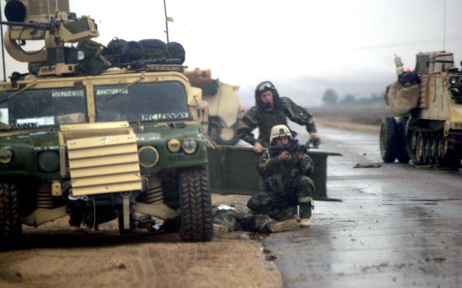 Capt. Scott Brannon, of the 1st Battalion, 15th Infantry Regiment, provides cover fire while medics rush to aid Spc. Shawn Williams, who was shot through the abdomen during an assault on a southern Iraq airfield in March 2003.
