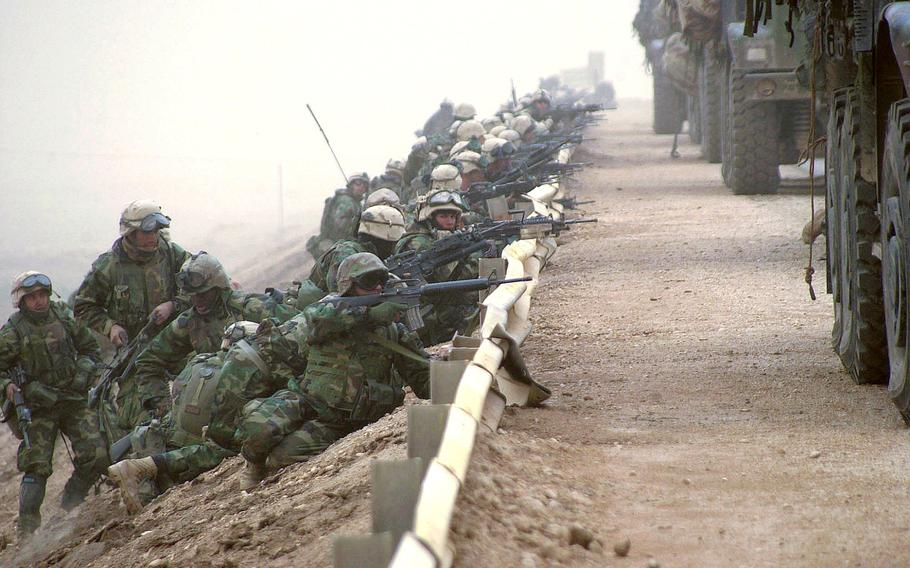 U.S. Marines line up behind a road barrier as they secure a key bridge along a main supply route during the march to Baghdad, Iraq in March 2003.