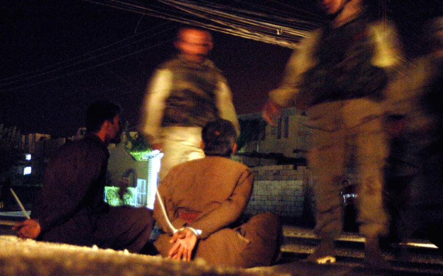 Two men arrested at a checkpoint are questioned after a 173rd Airborne Brigade soldier was wounded by celebratory gunfire in Kirkuk, Iraq, in May 2003.