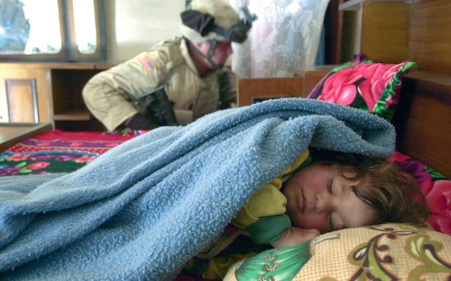 An Iraqi child sleeps while Spc. Jesse LeBlanc of the Black Sheep searches for weapons in a house near Taji, Iraq, in December 2004.