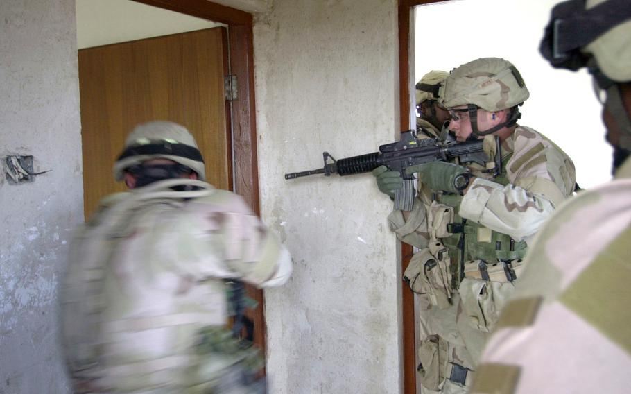 Soldiers from Company A, 1st Battalion, 69th Infantry Regiment, conduct a room-to-room search during a patrol of farmhouses near Taji, Iraq, in December 2004.