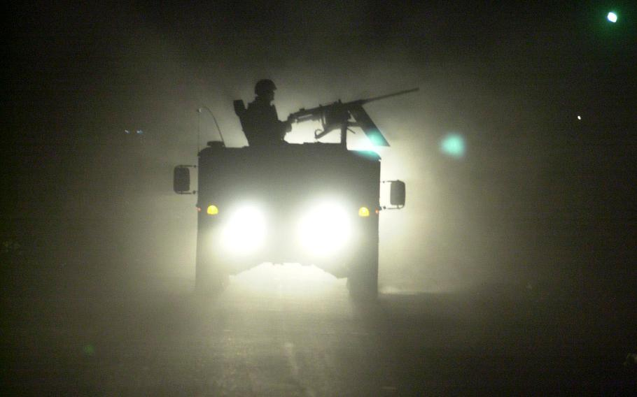 A Humvee gunner is outlined by the headlights of trailing vehicles as a convoy rolls through Baghdad at 3 a.m., on its way to a raid south of the city in October 2003. Soldiers often work around the clock in what they call the Three-Block War.