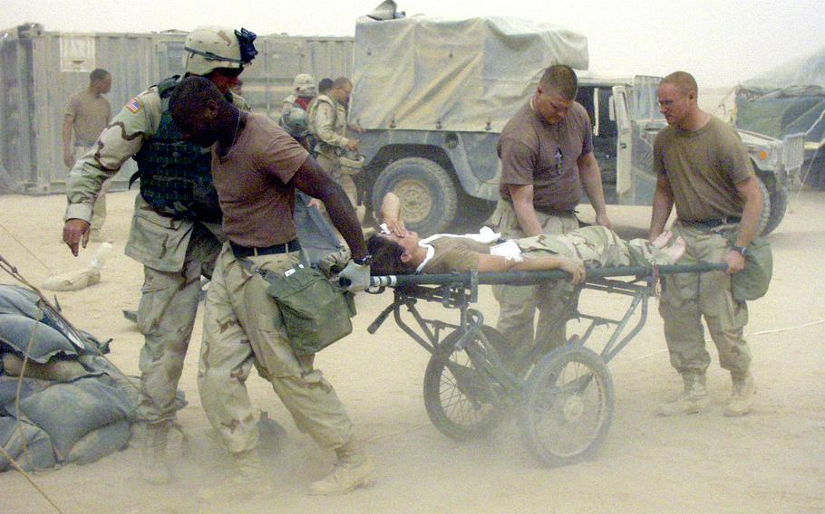 Medics wheel an injured soldier, just unloaded from a Black Hawk medevac helicopter, into the 212th Mobile Army Surgical Hospital during a sandstorm in central Iraq in April 2003.