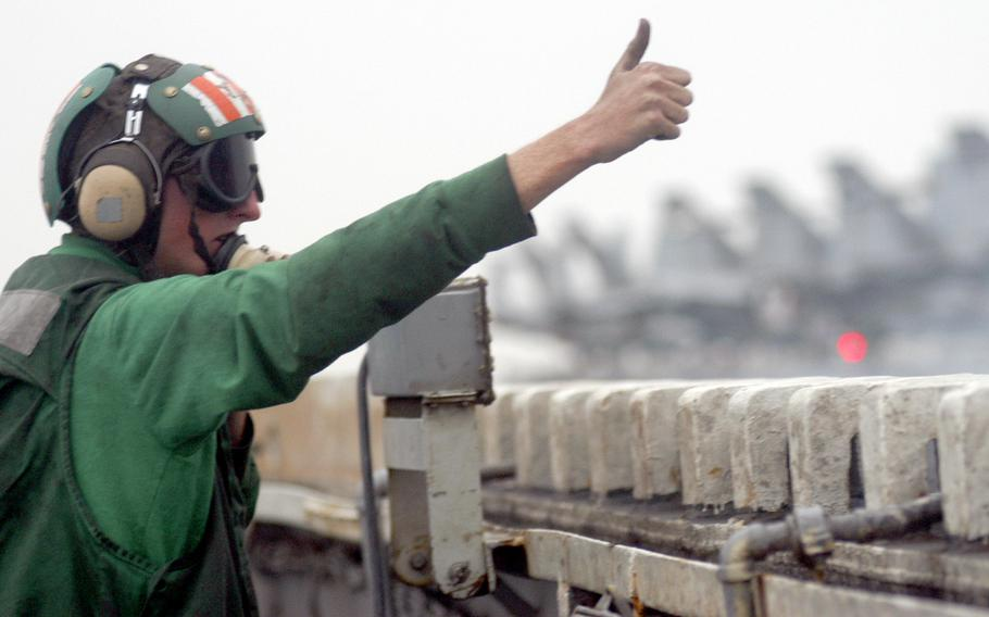 Petty Officer 2nd Class Eric Klostermann, an aviation boatswain's equipment mate, gives the thumbs-up for an aircraft to launch off the USS Kitty Hawk in March 2003.