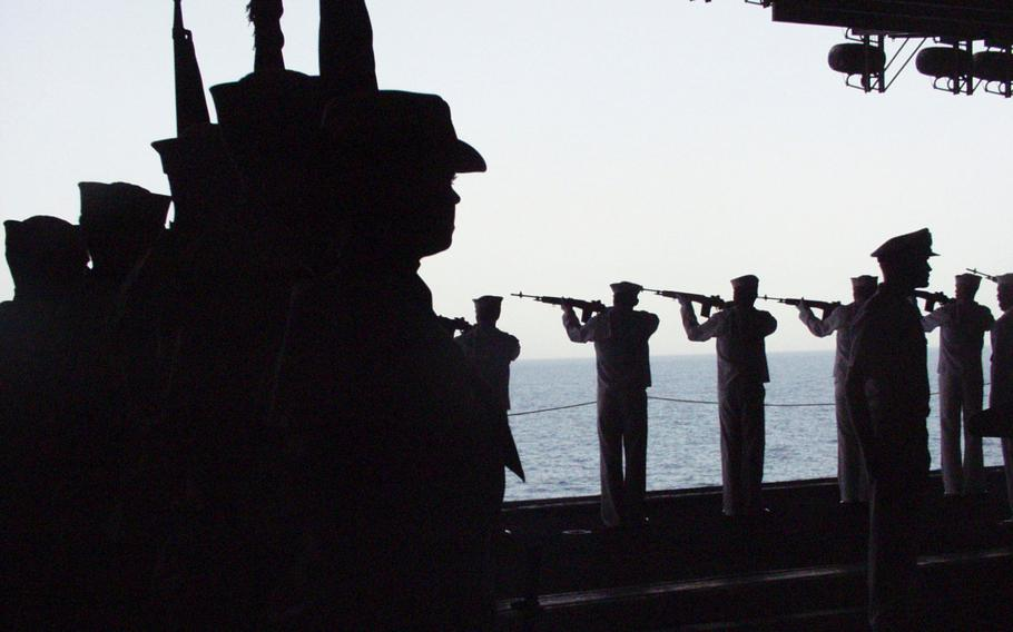 """Members of an honor guard, left, stand as sailors fire a 21-gun salute during an April 2003 memorial service aboard the USS Kitty Hawk for Lt. Nathan """"O.J."""" White, a Carrier Air Wing 5 member killed in combat."""