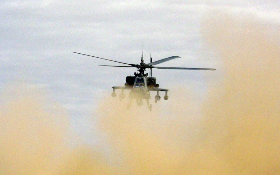 Chief Warrant Officer 3 Tim McCray and Chief Warrant Officer 2 Aaron Mitchell lift their AH-64A Apache off the ground en route to a mission against the former stronghold of the Iraqi Republican Guard's Medina Division, south of Baghdad in April 2003. The pilots are members of the 2nd Squadron, 6th Cavalry Regiment's Troop C.
