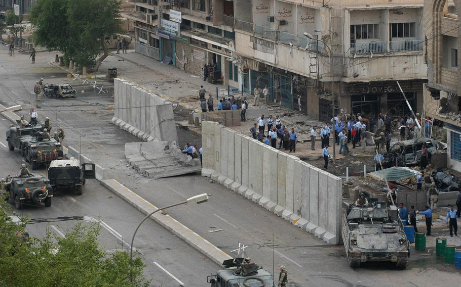 American soldiers and Iraqi police and security forces cordon off the scene of a car bombing near the Baghdad Hotel in October 2003. According to the 1st Armored Division's 1st Brigade commander, Col. Peter Mansoor, a car ran through a checkpoint at the hotel and came under fire.  Shortly thereafter, it exploded, killing six Iraqis and wounded at least 10 others, who were taken to local hospitals. One American soldier was slightly wounded and treated at the scene. Small units of soldiers share guard responsibilities at the Baghdad and two other nearby hotels with Iraqi police and protective forces.