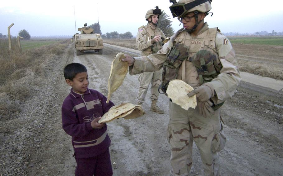 An Iraqi boy in Hora al Bosh gives freshly baked flatbread to Spc. Acisclo Melendez of Company A, 1st Battalion, 69th Infantry Regiment, in April 2003.