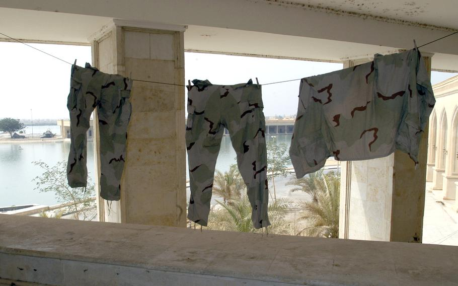 A set of BDUs hang from a second-floor balcony at Saddam Hussein's abandoned Al Faw Palace on Camp Victory near Baghdad International Airport, Iraq, in October 2003.